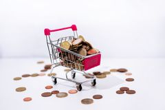 Small cart with coins on white background. Abstract composition of buying something. Small cart with coins on white background stock photo
