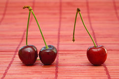 Abstract composition with fresh cherries, one without the pairs Stock Images