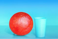 Abstract Composition With Red Ball. Red papier-mache ball and plastic cup on the turquoise and blue background - abstract geometric design with space for copy Stock Photos