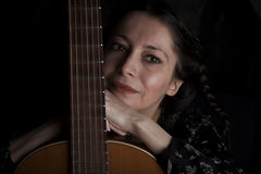 Beautiful woman leaning on guitar. Beautiful thoughtful woman leaning on guitars neck (closeup portrait over black, warm toning Stock Photos