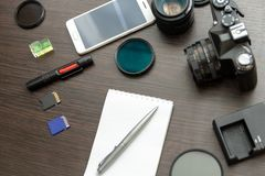 Abstract concept of modern photographer workplace. Dark desk with photography gear, camera, lenses and acessories royalty free stock photography