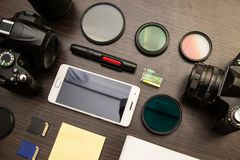 Abstract concept of modern photographer workplace. Dark desk with photography gear, camera, lenses and acessories royalty free stock photo