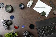 Abstract concept of modern photographer workplace. Dark desk with photography gear, camera, lenses and acessories stock photo