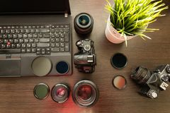 Abstract concept of modern photographer workplace. Dark desk with photography gear, camera, lenses and acessories stock photography