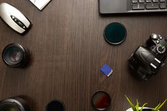 Abstract concept of modern photographer workplace. Dark desk with photography gear, camera, lenses and acessories royalty free stock images
