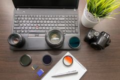 Abstract concept of modern photographer workplace. Dark desk with photography gear, camera, lenses and acessories royalty free stock photos