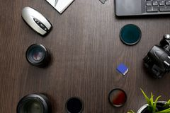 Abstract concept of modern photographer workplace. Dark desk with photography gear, camera, lenses and acessories stock image