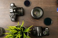 Abstract concept of modern photographer workplace. Dark desk with photography gear, camera, lenses and acessories royalty free stock image