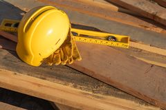 Abstract of Construction Hard Hat, Gloves and Level Resting on W stock images