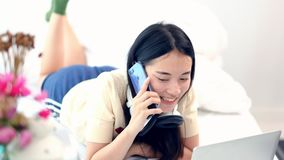 4K, Young asia woman talking on cellphone while lying in cozy bed at home in the morning. Cute teen girl makes a phone call her fr stock video footage