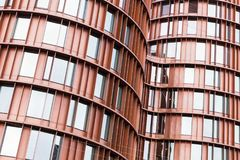 Curved walls made of red metal and glass. Abstract contemporary architecture background, curved walls made of red metal and glass Royalty Free Stock Photography