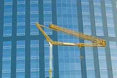 Abstract crop of modern office skyscraper. Height building. Abstract crop of modern office skyscraper. Vertical strips. With elevating crane before it Royalty Free Stock Image