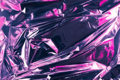 Abstract crumpled foil background. Grunge photo background. Neon colors. Pink and violet colors.  royalty free stock photo