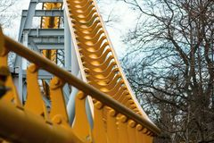 Abstract curved steel structure of yellow color. For an attraction in park under the open sky Royalty Free Stock Photos