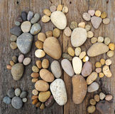 Abstract cute pebbles, footprint from boulder. Abstract cute concept on wood background from pebbles, amazing arranged boulder to family of footprint, awesome Royalty Free Stock Photo