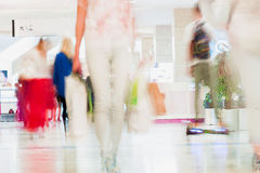 Abstract defocused motion blurred young people walking in the shopping center. Beautiful figure of a girl with shopping Royalty Free Stock Images