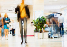 Abstract defocused motion blurred young people walking in the shopping center. Figure of one person close-up, urban Stock Image