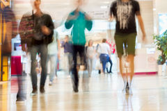 Abstract defocused motion blurred young people walking in the shopping center, urban lifestyle concept, background. Royalty Free Stock Photo
