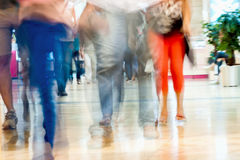 Abstract defocused motion blurred young people walking in the shopping center, urban lifestyle concept, background. Stock Photography
