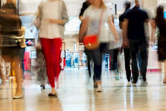Abstract defocused motion blurred young people walking in the shopping center, urban lifestyle concept. For background. Abstract blurred image of many people royalty free stock photography