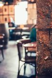 Abstract defocused shot of some chairs and people in a pub with. Bright light streaming through a window at the far end Stock Photo