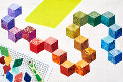 Abstract design of colorful pieces fabrics that look like cubes, quilting tools Royalty Free Stock Images