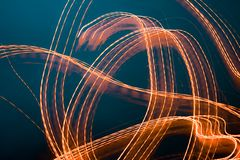 Abstract design of light painting. Orange lights against dark background royalty free stock photography
