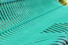 Abstract design of a teal park bench. A metal teal colored park bench displays a beautifully constructed abstract design Royalty Free Stock Images