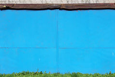 Abstract detailed blue metal wall background texture of sheet  painted with  paint, grass, sun visor  the roofing material and bri Stock Photos