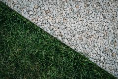 Abstract diagonal composition with green grass field and white stones surface texture, top view.  royalty free stock images