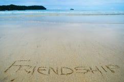 Abstract die teken van woordvriendschap op een achtergrond van het zandstrand wordt geschreven Royalty-vrije Stock Foto