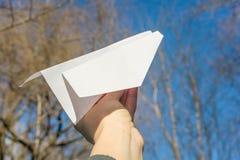 Abstract document in hand vliegtuig, blauwe hemel, de zonachtergrond van de lentebomen Royalty-vrije Stock Fotografie