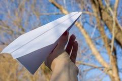 Abstract document vliegtuig, in hand, blauwe hemel, zonachtergrond Royalty-vrije Stock Afbeelding