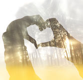 Abstract double exposion image of hands silhouette in the form of heart against the summer forest and sun flare light. Stock Photos