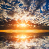 Abstract, dramatic sunset at the sea, ocean. Sun and clouds reflection in water royalty free stock photography