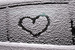 Abstract drawing of a heart on the side window of a car. Covered with wet snow royalty free stock images