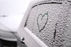 Abstract drawing of a heart on the side window of a car. Covered with wet snow stock photos
