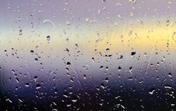 Abstract drops of rain water on window at sunset Stock Images