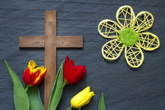 Abstract easter tulips and wooden cross on black marble. Concept Stock Image