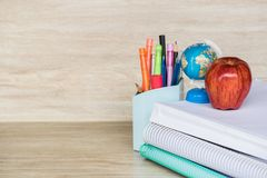 Abstract education, red apples, multicolored pens and white books with wooden backgrounds. Space stock photography