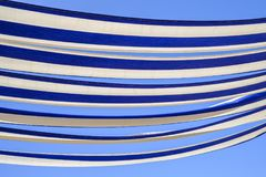 Blue and white awning. Abstract effect of the blue and white striped canvas of a restaurant awning in the sunshine against clear blue sky background royalty free stock image