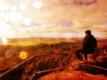 Abstract effect. Tourist sit on peak of sandstone rock and watching into colorful mist and fog in  morning valley. Man sit. Man in jeans.Fall mountain mist Stock Image