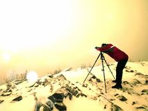 Abstract.  Travel photographer doing pictures in ancient stones on snowy peak Stock Image