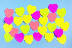 Abstract empty sticky note in the shape of a heart magnet on blue board stock photography