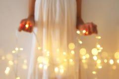 Abstract en bokeh beeld van de jonge lichten van de slingerkerstmis van de vrouwenholding Stock Fotografie