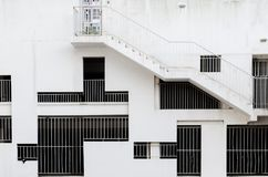 Abstract exterior architectural background - grille windows of different shapes and sizes at white concrete wall. An external staircase on building, covered Royalty Free Stock Photos