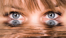 Abstract eyes with water. Beautiful woman eyes reflected in the water Stock Photography