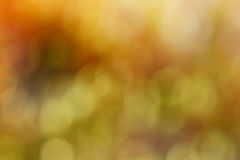 Abstract fall colored bokeh  background. Blurred fall colors of red, orange, green, and brown Royalty Free Stock Photos