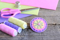 Abstract felt round flower with light pink beads. Handmade bright felt flower, scissors, thread, colorful felt sheets, thimble Stock Photo