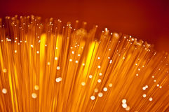 Abstract fibre optic glow. Close up on the ends of many illuminated fibre optic light strands with vibrant warm colours Royalty Free Stock Images